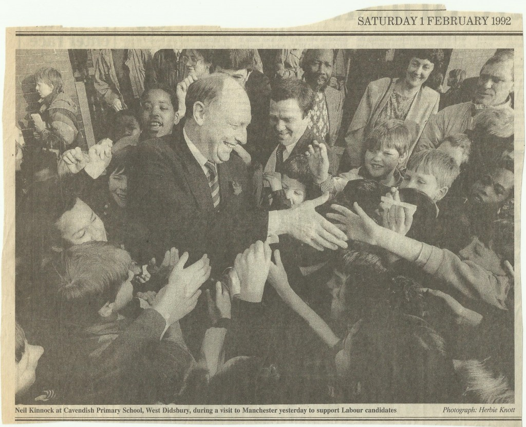 Neil Kinnock in a crowd of children and adults with Kath Fry in the background.